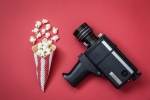 Cone and popcorn with vintage video camera on red background, cinema creative concept.