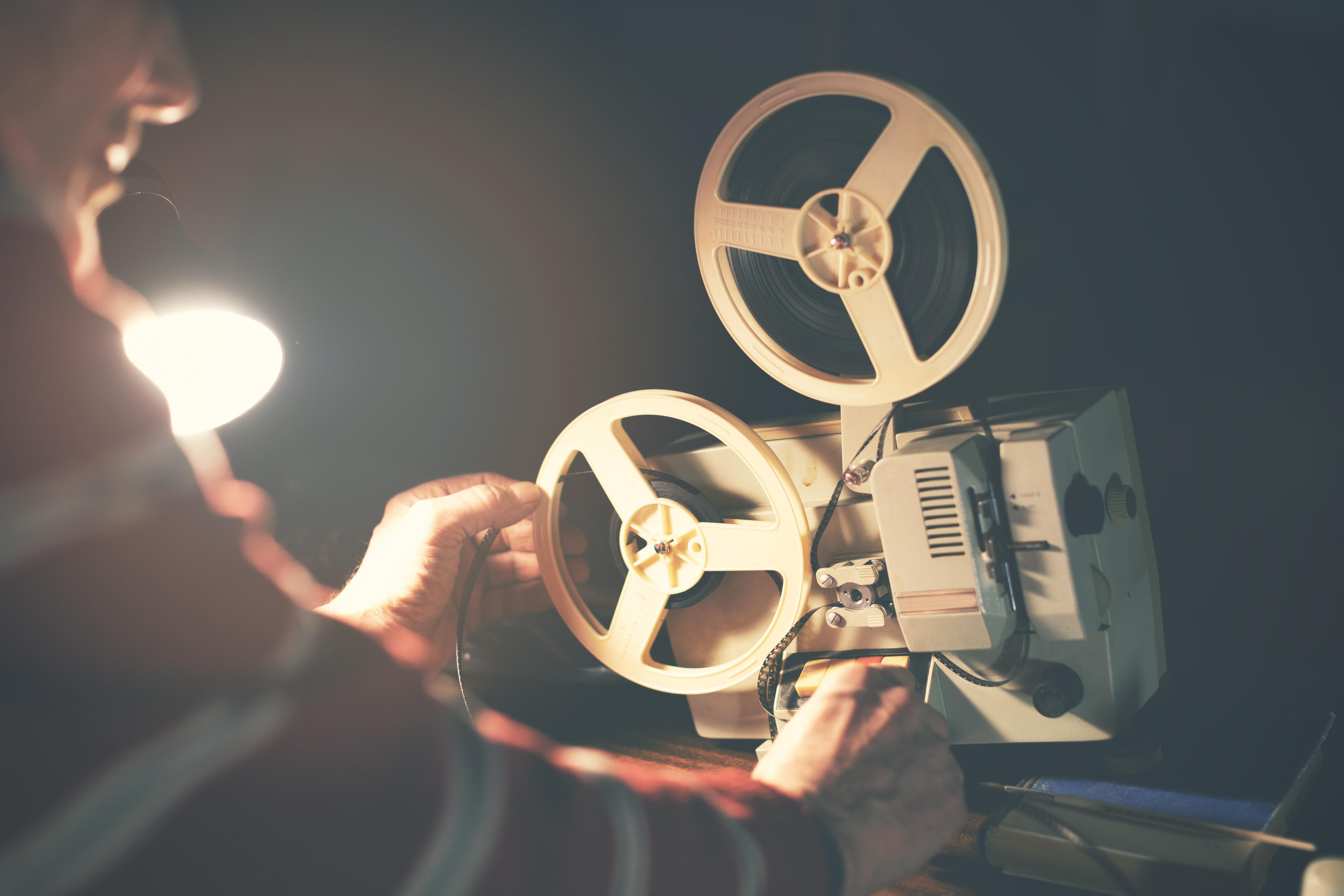 man set up film reel on vintage 8mm movie projector in dark room